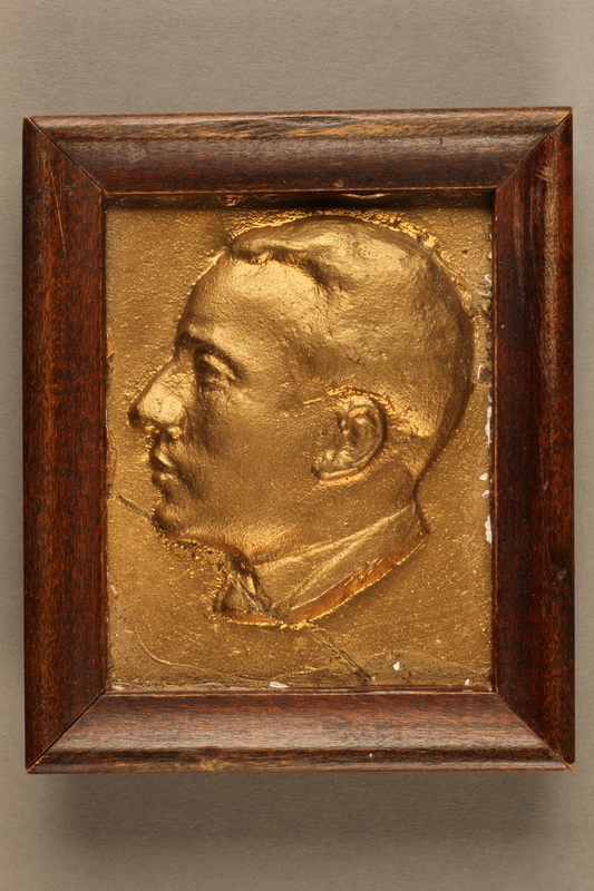 2018.286.5 front Framed, gold-colored plaque depicting a Jewish Hungarian banker