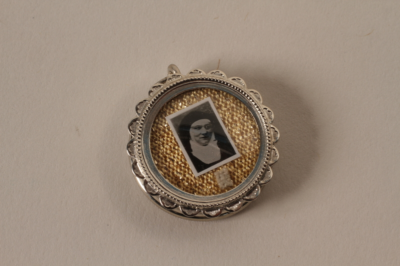2001.62.3 closed Small case with photo of a nun containing a red seal with a shield crest