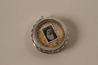 2001.62.3 closed Small case with photo of a nun containing a red seal with a shield crest  Click to enlarge