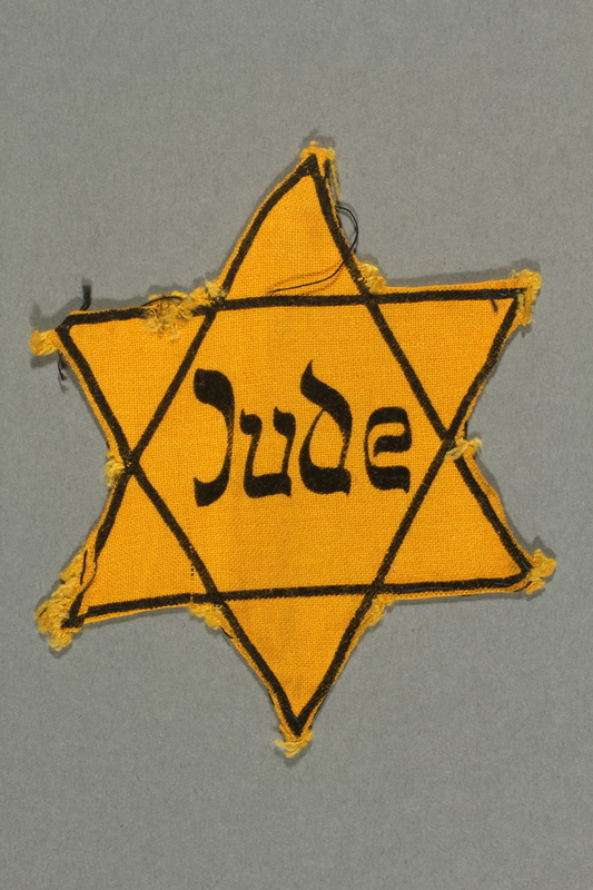 2018.395.2 front Factory-printed Star of David badge acquired by a Polish Jewish refugee and activist