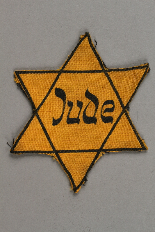 2018.427.4 front Factory-printed Star of David badge printed with Jude, belonging to a German Jewish prisoner