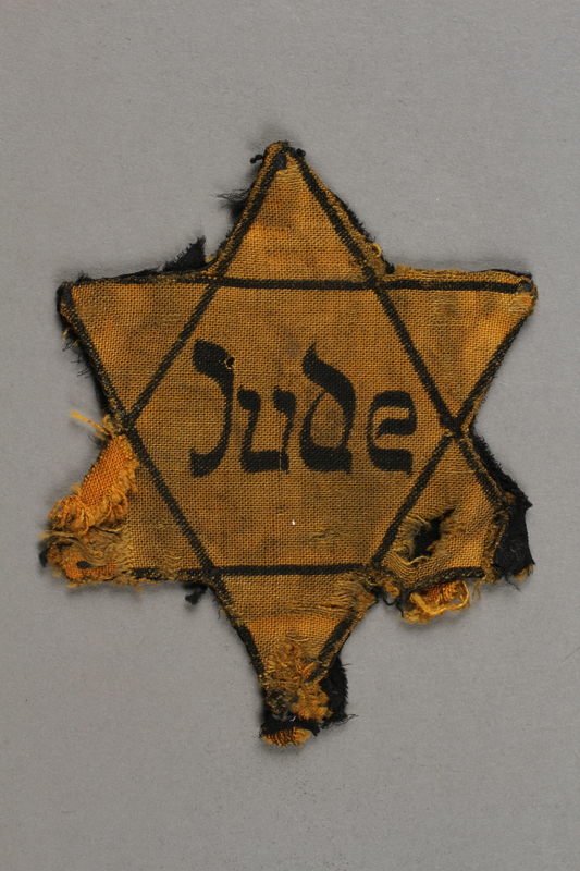 2018.427.5 front Factory-printed Star of David badge printed with Jude, worn by a German Jewish prisoner