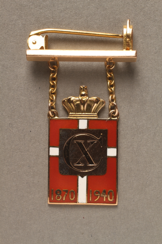 2018.497.1 front Kingmark gold, red, and white enamel pin with chains on a pinbar commemorating the 70th birthday in 1940 of King Christian X of Denmark