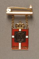 2018.497.1 front Kingmark gold, red, and white enamel pin with chains on a pinbar commemorating the 70th birthday in 1940 of King Christian X of Denmark  Click to enlarge