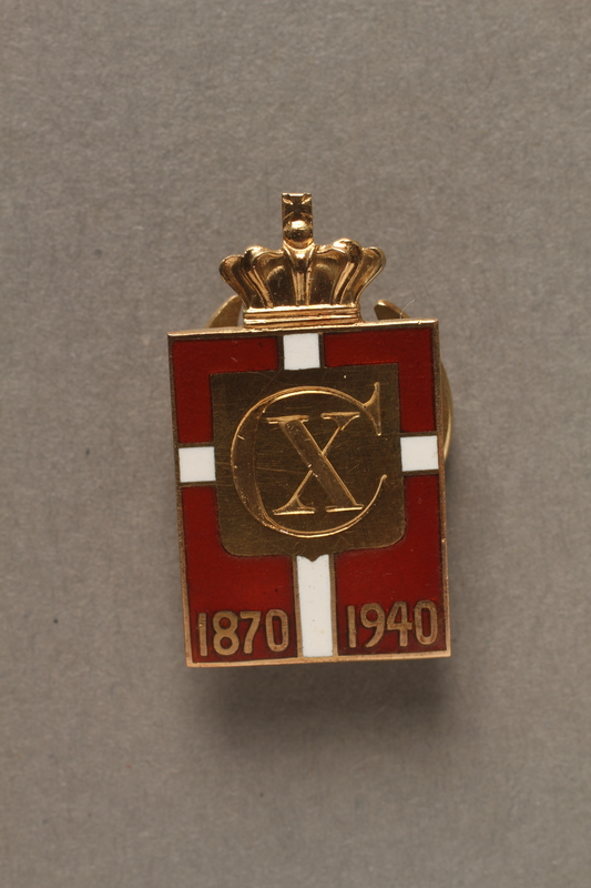 2018.497.2 front Kingmark gold, red, and white enamel pin on a buttonhole back commemorating the 70th birthday in 1940 of King Christian X of Denmark