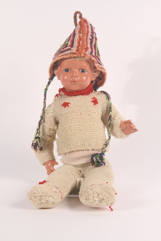 1992.4.1 a-f front Doll's offwhite hand knit wool sweater and pants with red flowers made by a young girl after her release from Theresienstadt