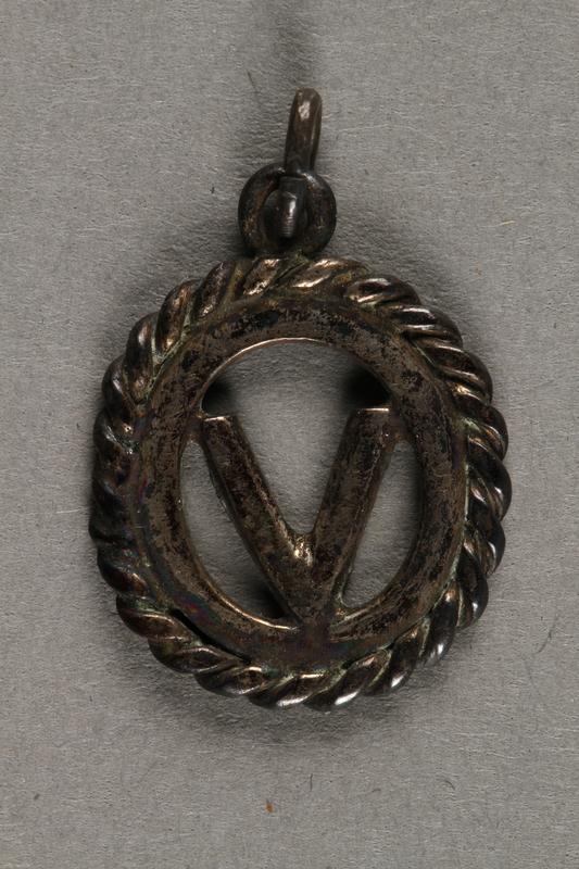 """2019.183.8 front """"V"""" pendant or charm, made by Vapniarka prisoners"""