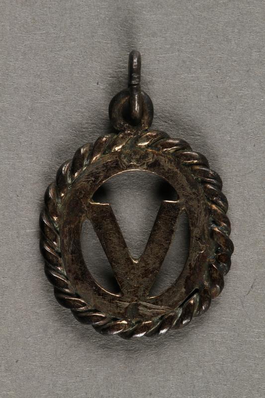 """2019.183.8 back """"V"""" pendant or charm, made by Vapniarka prisoners"""