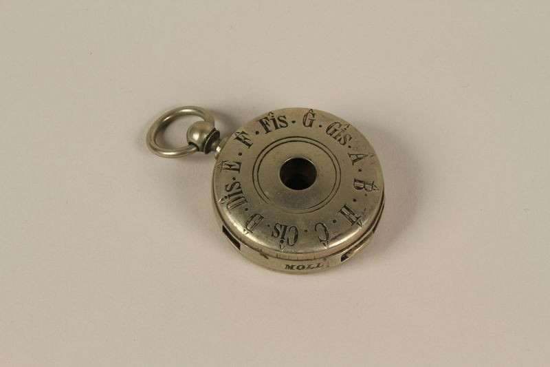 1992.8.2_a front Circular silver 12 tone pocket watch style pitch pipe and case used by a cantor