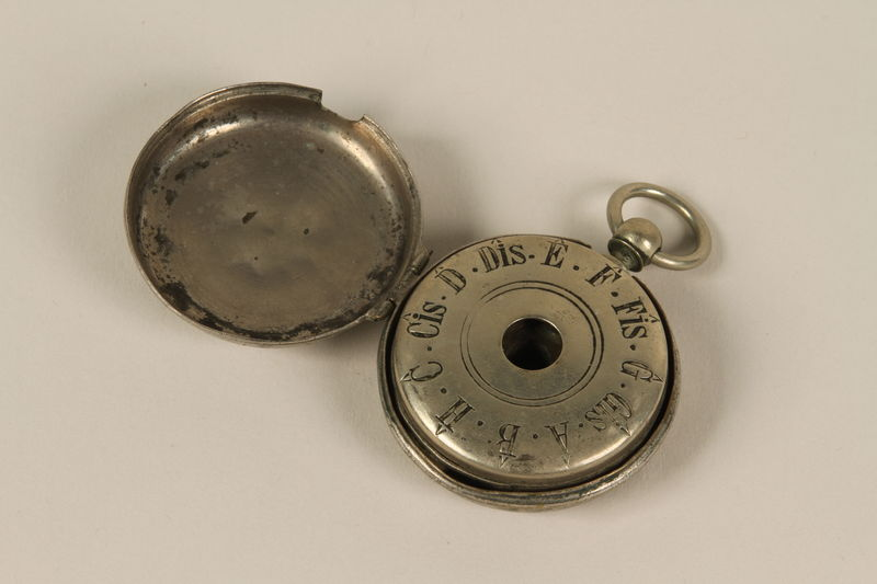1992.8.2_a-b open Circular silver 12 tone pocket watch style pitch pipe and case used by a cantor