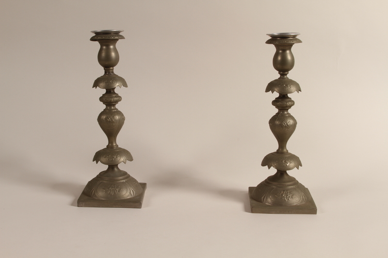 1992.8.28 a-d front Pair of Sabbath candlesticks with wax reservoirs owned by a Jewish refugee