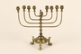 Brass Hanukkah menorah with fish shaped feet used by a Jewish refugee family
