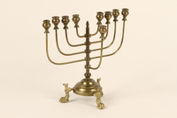 1992.8.32 side Brass Hanukkah menorah with fish shaped feet used by a Jewish refugee family  Click to enlarge