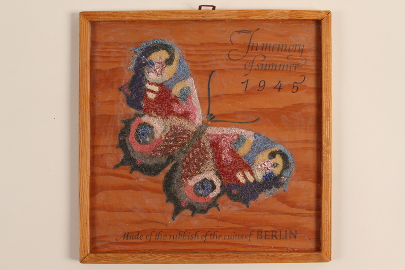 1993.100.1 front Wooden sign with a painted butterfly made from trash found in postwar Berlin