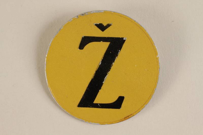 1993.113.1 front Yellow metal badge with a brown Croatian letter Z to identify a Jew