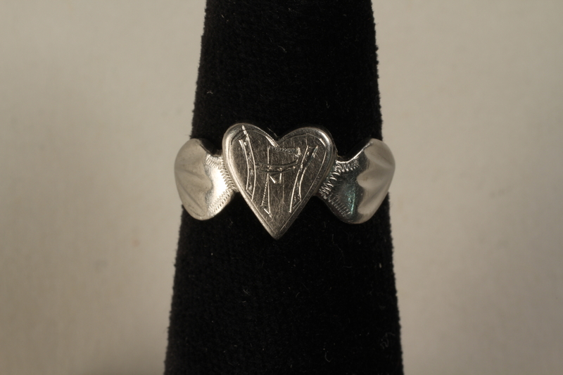 1993.158.1 front Engraved heart shaped ring crafted from munitions parts and made in secret in a slave labor camp