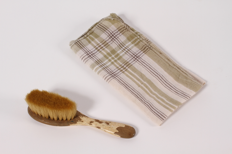 2012.249.1 a-b front Child's hairbrush and plaid handkerchief used by a young Jewish Polish refugee
