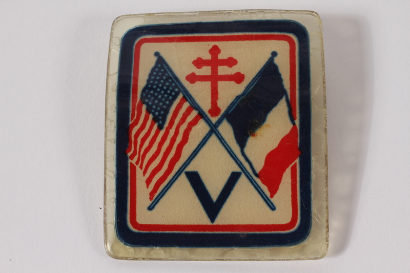 2004.248.7 front France Forever laminated pin with a V and US & French flags owned by a Jewish French resistance member