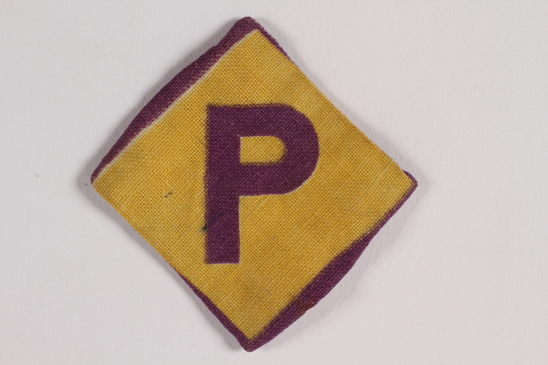 2013.397.2 front Forced labor badge, yellow with a purple P, worn by a Catholic Polish soldier interned by the Germans