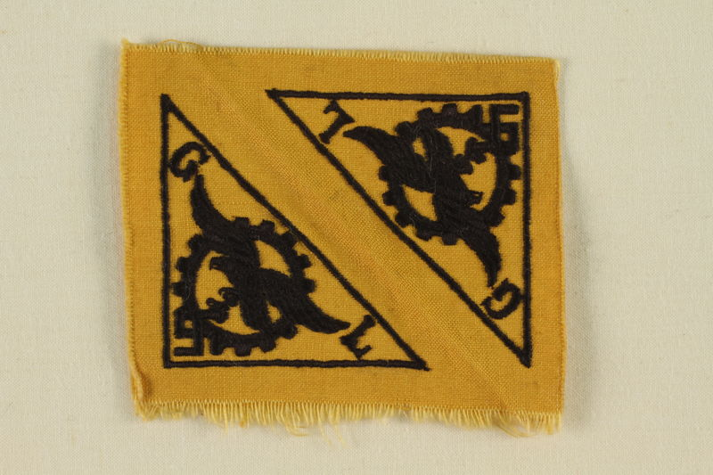 1993.26.1 front Gold colored patch with 2 triangles with a Reichsadler and the letters G L