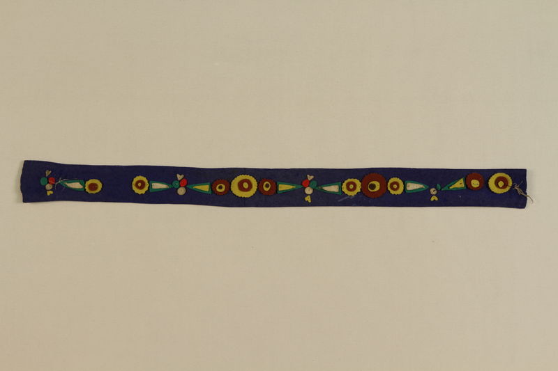 1988.99.1 front Blue felt belt with appliqued flowers found by a German Jewish teenage inmate at Auschwitz