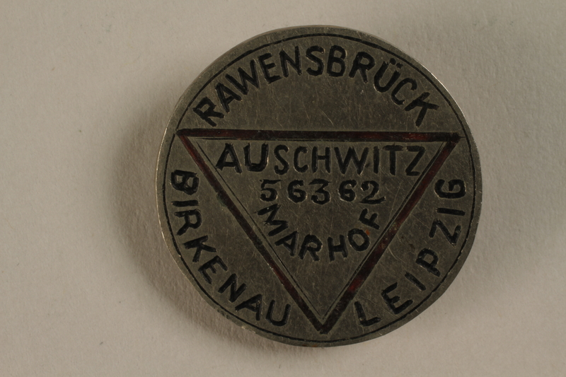 1993.27.34 front Metal pin made for a former concentration camp inmate with her prisoner number and the camps where she was held