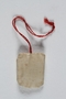 Small white bag with a button saved from the coat of a young Jewish girl deported to Auschwitz