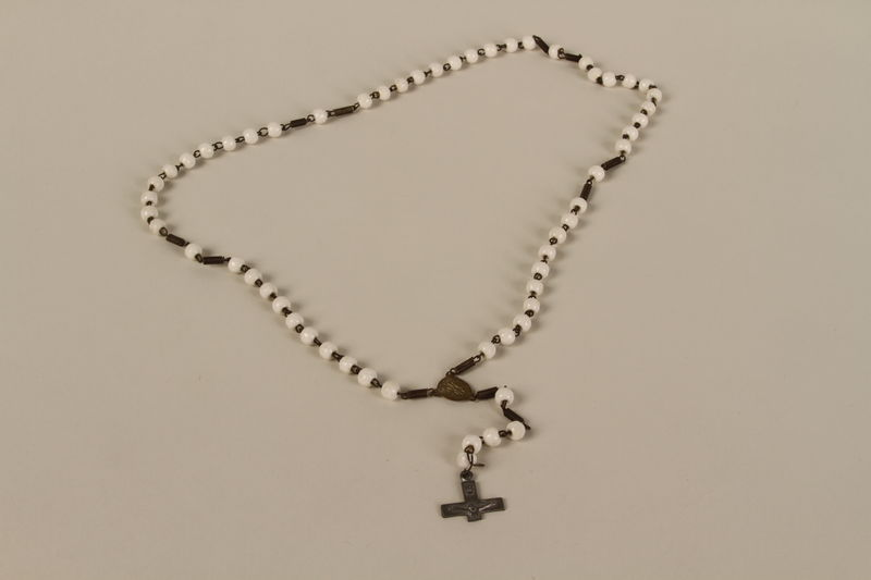 1993.83.1 front White bead rosary on a chain with a cross