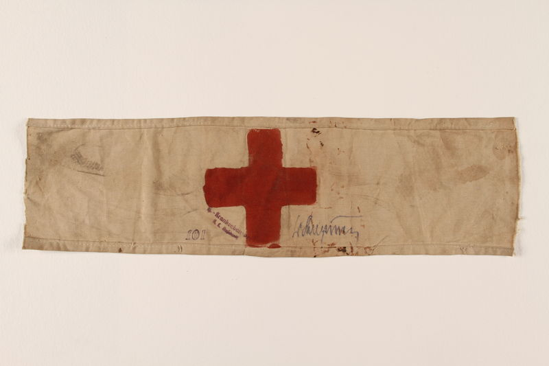 1993.90.5 front White armband with a red cross worn by a concentration camp inmate