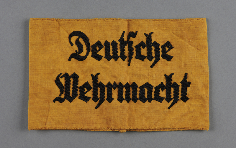 2013.453.6 front Yellow armband embroidered Deutsche Wehrmacht for use by laborers acquired by a US soldier