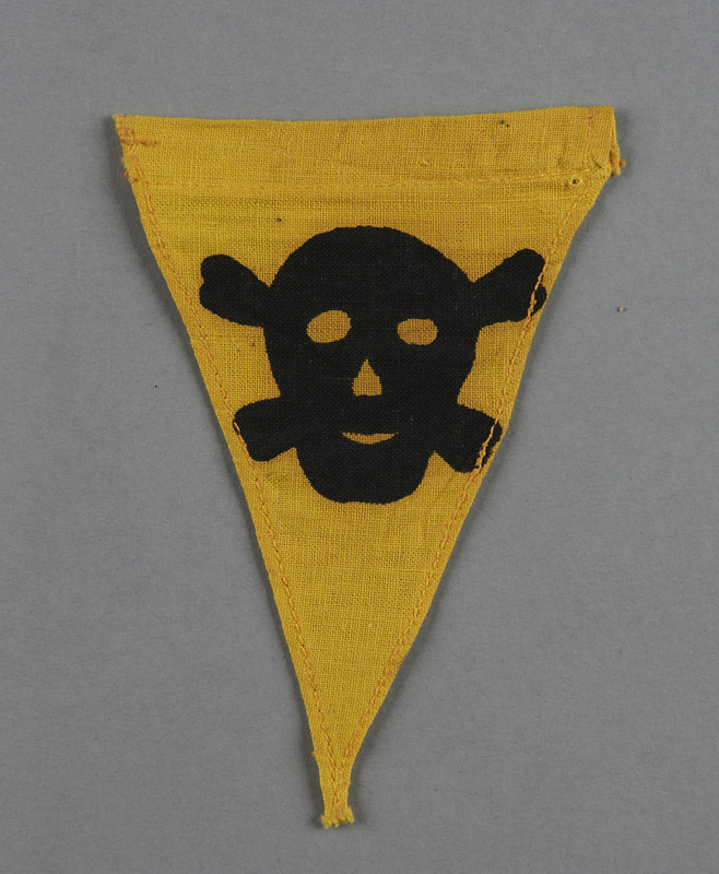 2013.453.7 front Small, yellow warning pennant with a skull and crossbones acquired by a US soldier