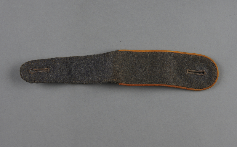 2013.453.8 front Wehrmacht shoulder board in gray with gold trim acquired by a US soldier