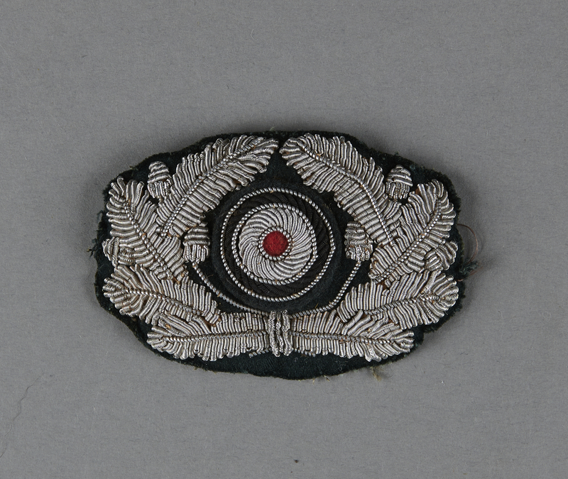 2013.453.10 front German Army officer's visor cap insignia with a silver wire oak leaf wreath and cockade acquired by a US soldier