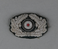 2013.453.10 front German Army officer's visor cap insignia with a silver wire oak leaf wreath and cockade acquired by a US soldier  Click to enlarge