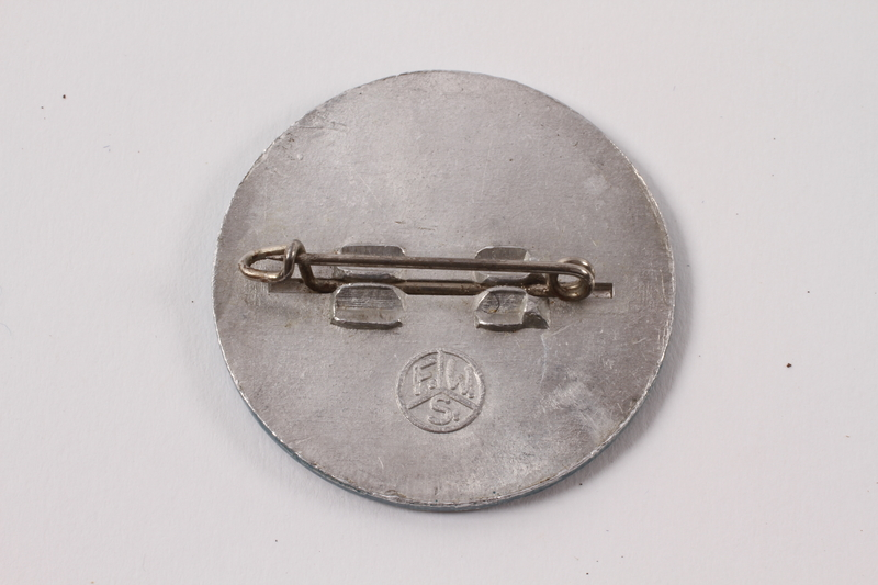 2013.474.2 back Blue and silver HIAS pin worn by a Jewish Latvian youth postwar