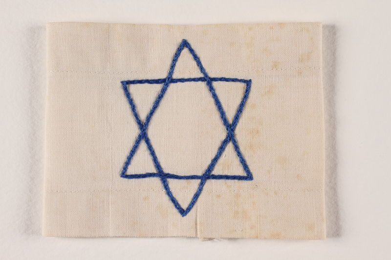 1994.6.2 front White armband with a blue chain stiched embroidered Star of David