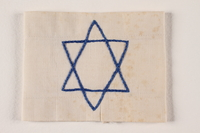 1994.6.2 front White armband with a blue chain stiched embroidered Star of David  Click to enlarge