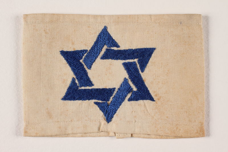 1994.6.3 front White armband with a blue satin stiched embroidered Star of David