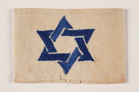 1994.6.3 front White armband with a blue satin stiched embroidered Star of David  Click to enlarge
