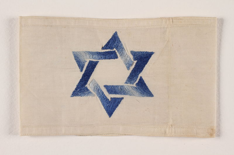 1994.6.4 front White armband with a Star of David embroidered in blue and white