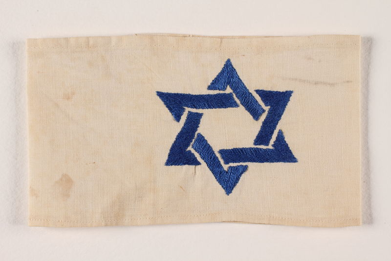 1994.6.5 front White armband with a Star of David embroidered in blue and white