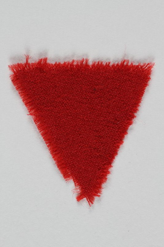 1995.105.2 front Red wool triangular inmate badge retrieved by a US soldier at a concentration camp