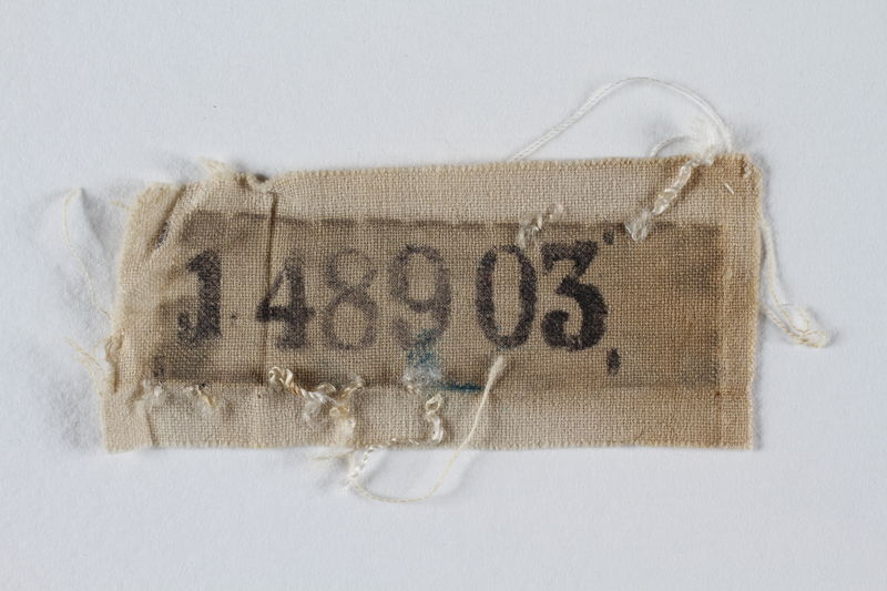 1995.105.3 front White cloth badge with a stencilled prisoner number retrieved by a US soldier