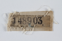 1995.105.3 front White cloth badge with a stencilled prisoner number retrieved by a US soldier  Click to enlarge