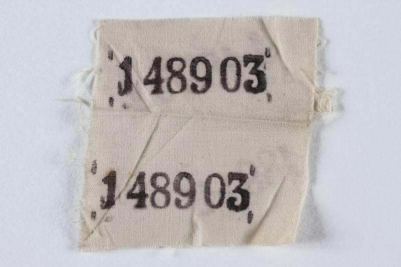 1995.105.4 front White cloth badge with 2 stencilled prisoner numbers retrieved by a US soldier