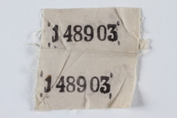 1995.105.4 front White cloth badge with 2 stencilled prisoner numbers retrieved by a US soldier  Click to enlarge