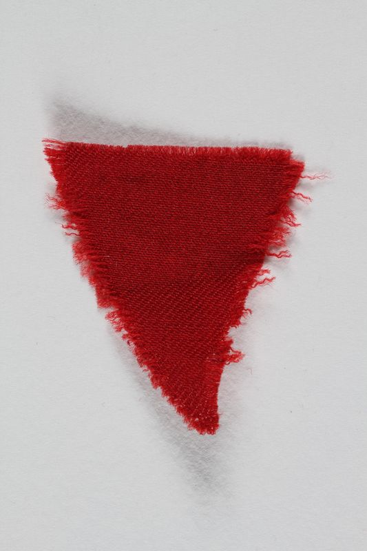 1995.105.9 front Red wool triangular inmate badge retrieved by a US soldier at a concentration camp