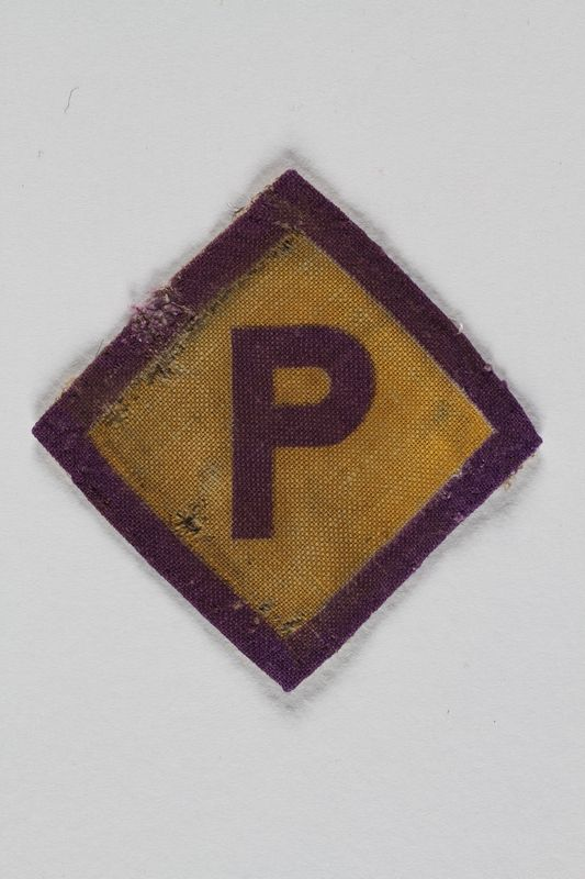 1995.107.1 front Forced labor badge, yellow with a purple P, to identify a Polish forced laborer acquired by a US soldier