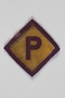 Forced labor badge, yellow with a purple P, to identify a Polish forced laborer acquired by a US soldier