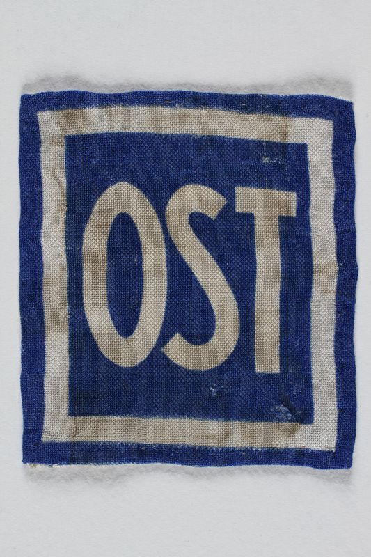 1995.107.2 front Forced labor badge, blue field with OST in white letters, to identify a forced laborer from the Soviet Union